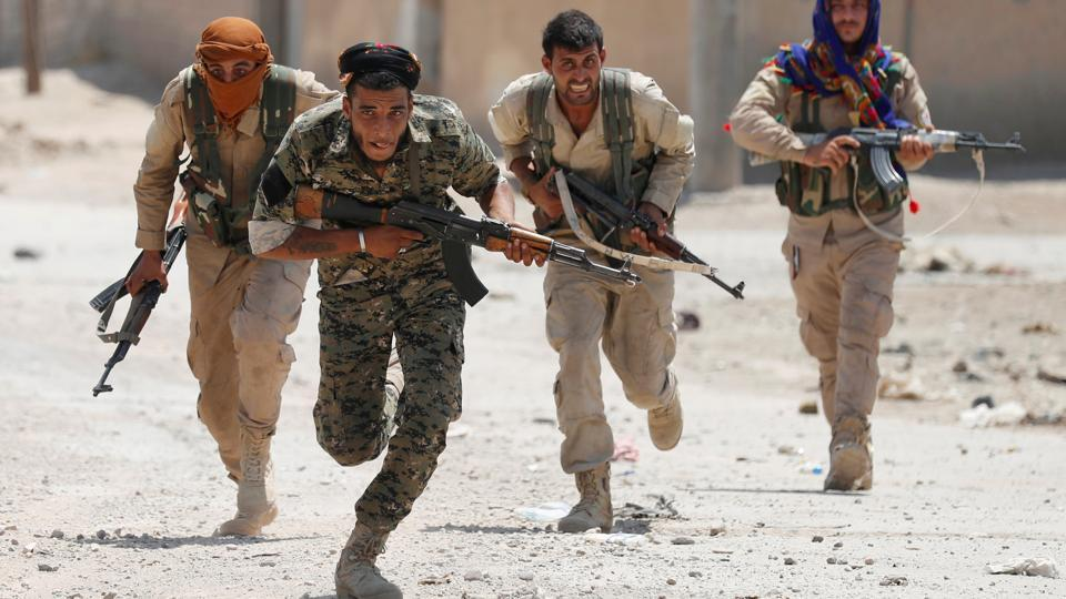 Kurdish fighters from the People's Protection Units (YPG) run to cover in Raqqa, Syria. In one village, a single IS sniper hunkered down in a house held up hundreds of Kurdish fighters, US special forces and 40 vehicles. Eventually, his rifle went silent after three air strikes on the house. IS fighters were experts at suicide bombings and assembling homemade bombs. Many houses were booby-trapped. Iraqi military commanders had to factor these perils into their warplans. (Goran Tomasevic / REUTERS)