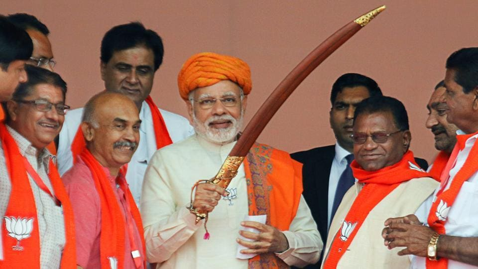 Prime Minister Narendra Modi being presented a sword by supporters during an election campaign rally.
