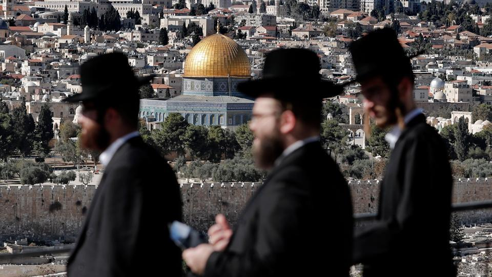 "Ultra Orthodox Jews are seen in the city of Jerusalem with the Dome of the Rock mosque in the background, on December 4, 2017. US officials on condition of anonymity said Trump will again sign the waiver but will also instruct the State Department to begin the multi-year process of moving the embassy. The officials say the recognition of Jerusalem as Israel's capital will be an acknowledgement of ""historical and current reality"" rather than a political statement. (Thomas Coex / AFP)"