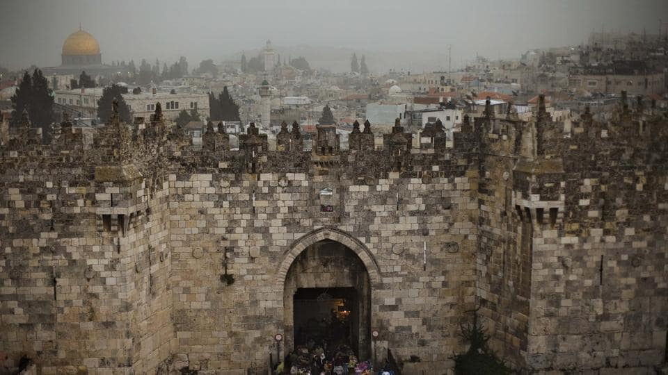 In this Feb. 19, 2009 photo, people walk in and out of the Damascus gate, while the Dome of the Rock, background and left, is seen on a cloudy, overcast day in Jerusalem's Old City.