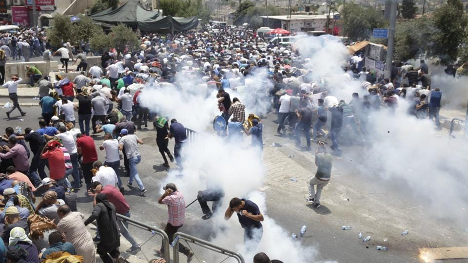 Palestinians evade tear gas thrown by Israeli police outside the Old City on July 21, 2017. Israeli security officials say they are monitoring the situation for all scenarios. Much of the violence between Israel and the Palestinians over the past 20 years has been connected to the holy city. More recently, a wave of Palestinian stabbings erupted in late 2015 in part due to growing numbers of Jewish nationalists heading to the Temple Mount. (Mahmoud Illean / AP)
