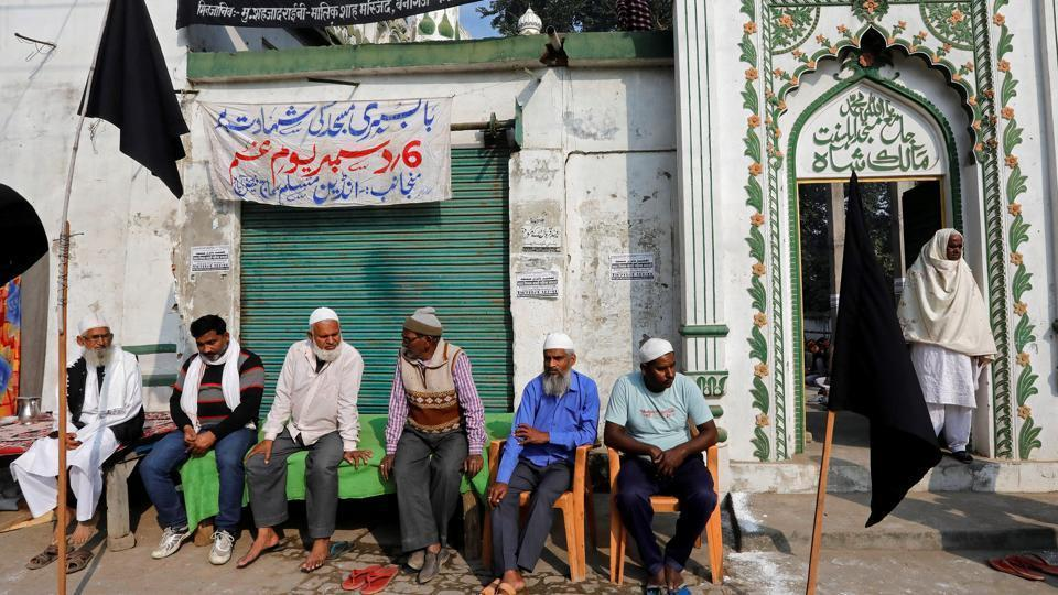 Muslims sit outside a mosque as they observe a black day marking the 25th anniversary of the razing of a 16th century Babri mosque in Ayodhya.