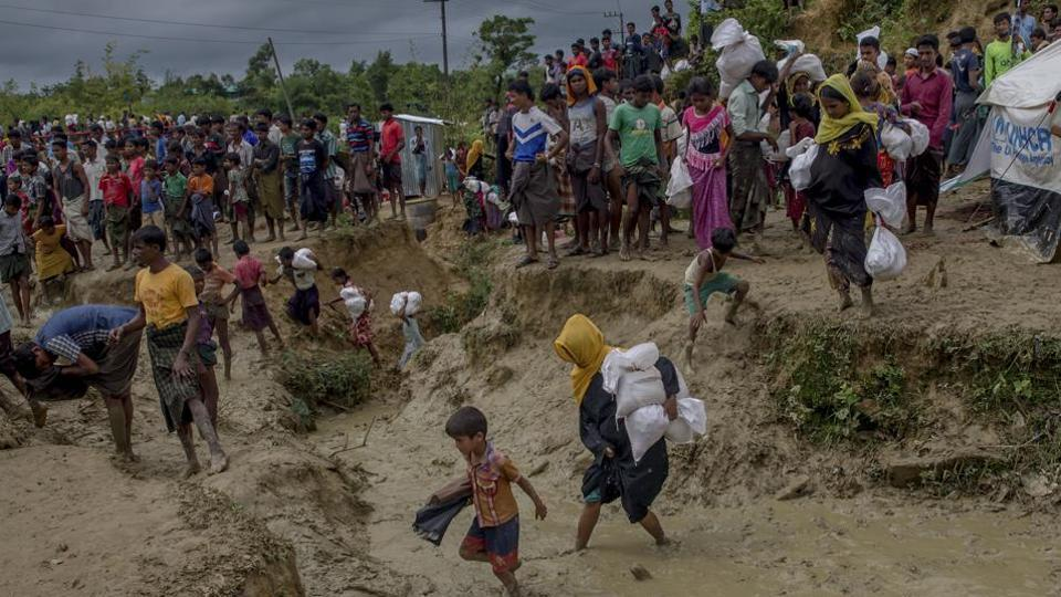 In this Sept. 28, 2017 file photo, Rohingya Muslims, who crossed over from Myanmar into Bangladesh, walk through muddy field after collecting aid from a distribution centre near Balukhali refugee camp, Bangladesh.