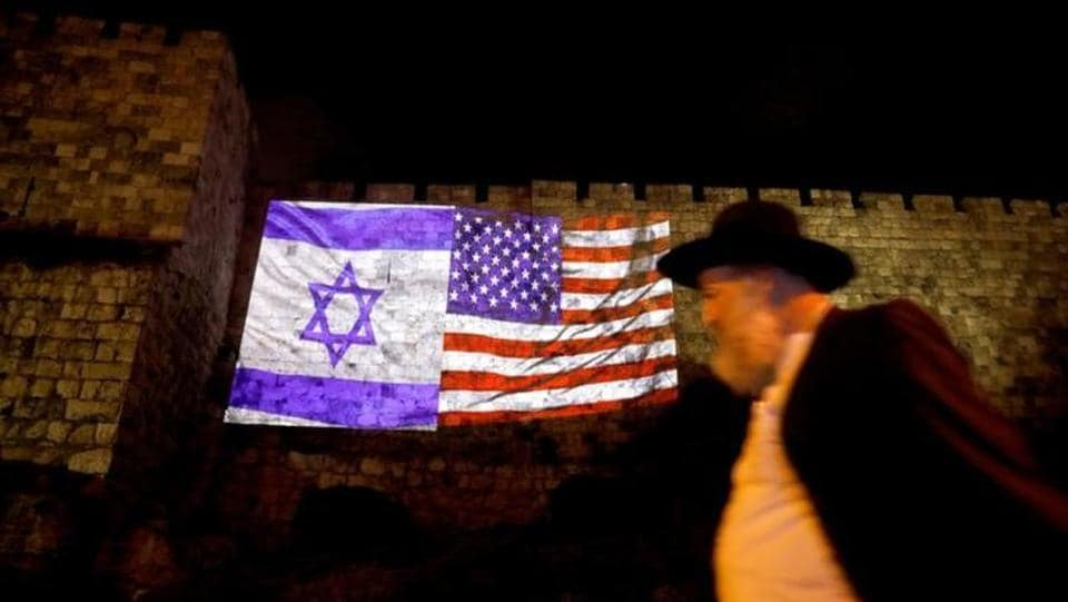 An Israeli man passes the Israeli flag and an American one projected on a part of the walls surrounding Jerusalem's Old City on December 6, 2017. Trump's recognition of Jerusalem isolates the United States on one of the world's most sensitive diplomatic issues. It drew a storm of criticism from Arab and European leaders, including some of America's closest allies. (Ronen Zvulun / REUTERS)