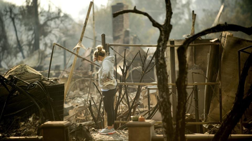 Bree Laubacher pauses while sifting through rubble at her home on Wednesday. Back in the beachside city of Ventura, the fire killed more than two dozen horses at a stable and had destroyed at least 150 structures, a number that is expected rise as firefighters assess losses. (Noah Berger / AP)