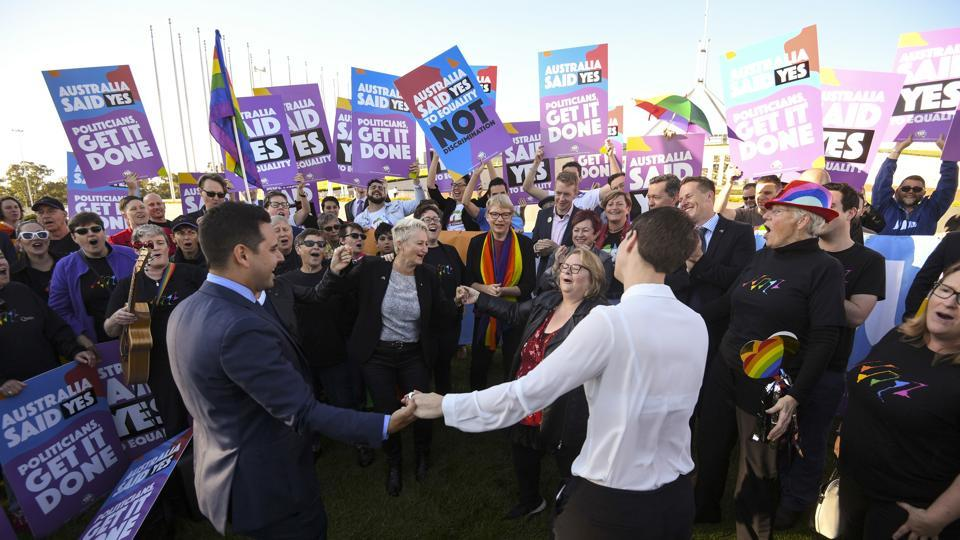 Same-sex marriage campaigners and volunteers cheer as they call on politicians to pass marriage equality legislation during rally outside Parliament House in Canberra, Australia.
