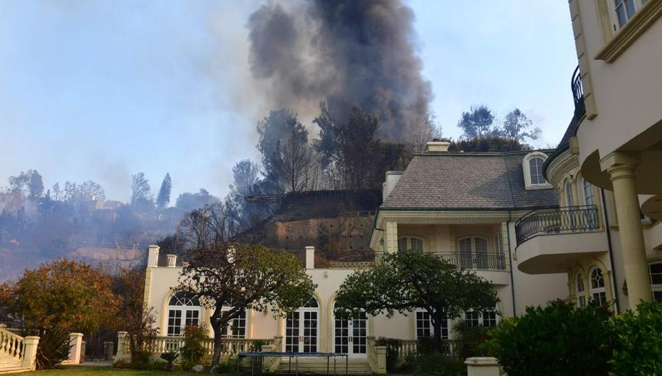 A huge plume of black smoke rises from a burning home on a hilltop beside one still standing in Bel Air, east of the 405 freeway on December 6, 2017 in Los Angeles.