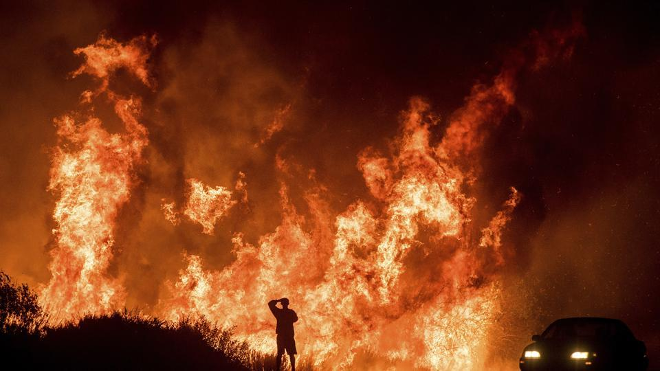 A motorists on Highway 101 watches flames from the Thomas fire leap above the roadway north of Ventura, California.