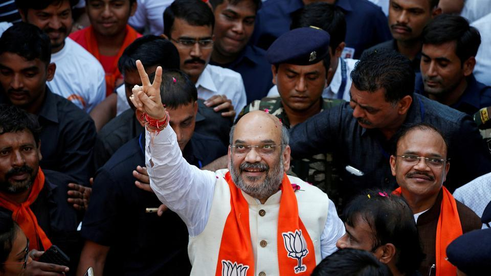 BJP chief Amit Shah gestures as he goes on a door-to-door campaign at a residential area for the upcoming Gujarat state assembly elections, in Ahmedabad.