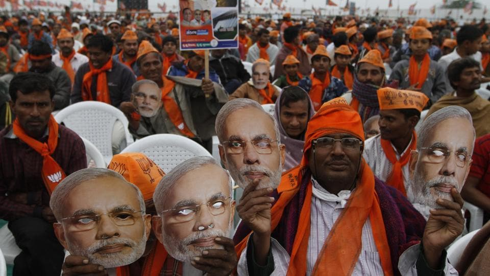 Supporters of Prime Minister Narendra Modi hold his masks during an election campaign rally at Dhandhuka in Gujarat.