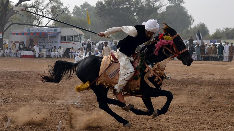 A Pakistani rider charges across a course holding a lance to pick up pegs at a tent-pegging competition during an annual festival at the village of Kot Fateh Khan in Attock, Punjab province. Festooned with garlands and colourful bridles, turbaned riders mounted on horseback gallop, aiming at tiny wooden blocks keeping alive a centuries-old tradition of tent-pegging in Pakistan. (Aamir Qureshi / AFP)