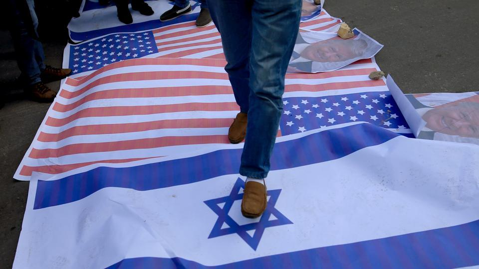 Palestinian protesters step on US and Israeli flags following US President Donald Trump's decision to recognise Jerusalem as the capital of Israel, in Gaza City.