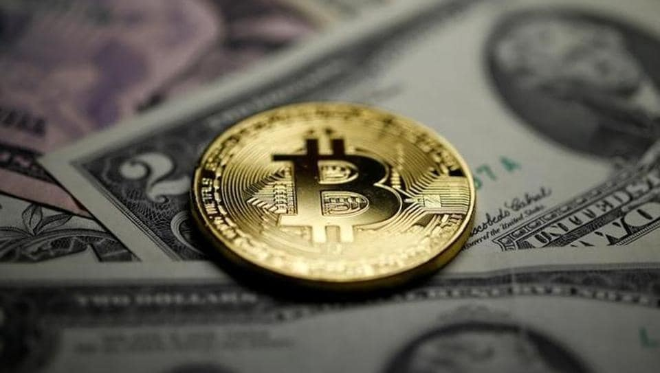A Bitcoin and Dollar notes are seen in this illustration picture taken September 27, 2017.