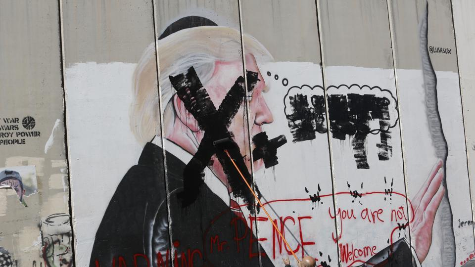 A Palestinian paints over a poster of the US President Donald Trump during a protest in Bethlehem, West Bank.