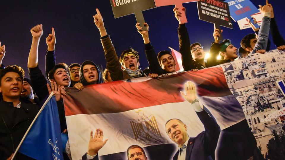 "Meanwhile in Istanbul, protesters chanted slogans with posters of Turkish President Recep Tayyip Erdogan and Egypt's former president Mohamed Morsi reading ""There is no you or me, there is Jerusalem- Killer Israel get out of Palestine"" during a demonstration against the US and Israel at Fatih Mosque. (Yasin Akgul / AFP)"
