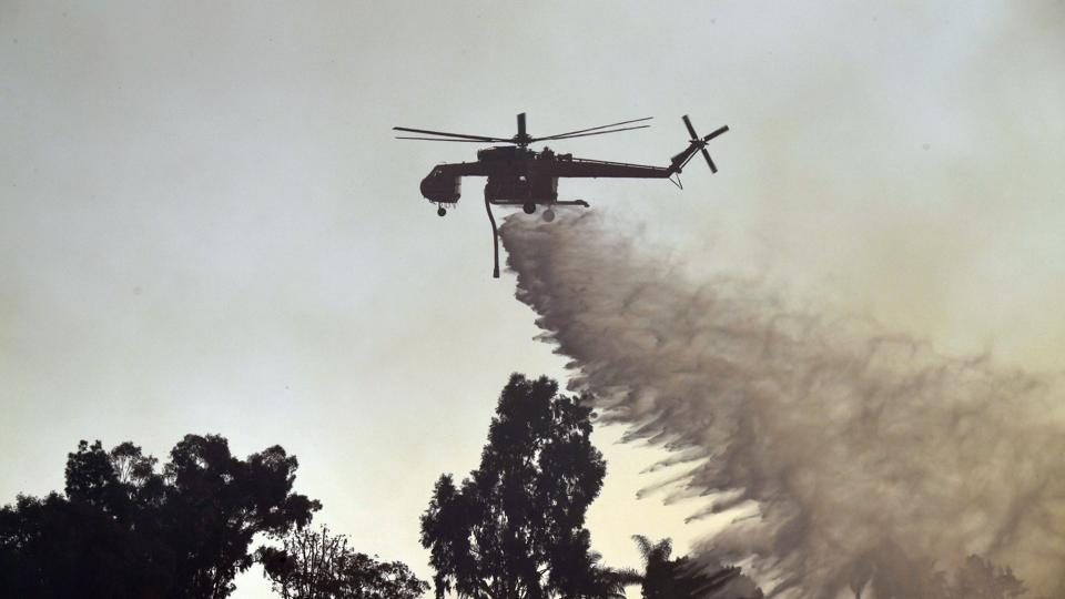 A helicopter drops water on the Skirball fire in west Los Angeles on December 6, 2017. California's fire season usually ends in November but the hottest summer on record and delayed rains have left the region tinder-dry into December. Some scientists have linked the conditions to climate change. The Skirball fire is likely to last several more days. (Robyn Beck / AFP)