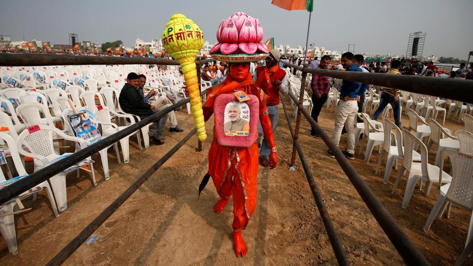 A supporter carries overhead a model of lotus, the election symbol of Bharatiya Janata party (BJP), as he arrives to attend a campaign meeting addressed by PM  Narendra Modi ahead of Gujarat state assembly election in Ahmedabad. (Amit Dave / REUTERS)