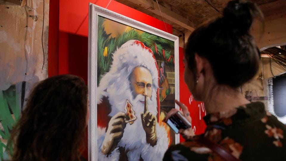 Visitors look at a painting depicting Russian president Vladimir Putin as Father Frost, the Russian equivalent of Santa Claus, at the exhibition. These aren't his latest series of publicity photos, but rather artwork at a new Moscow exhibition focussed on Russia's leader. (Maxim Shemetov / REUTERS)