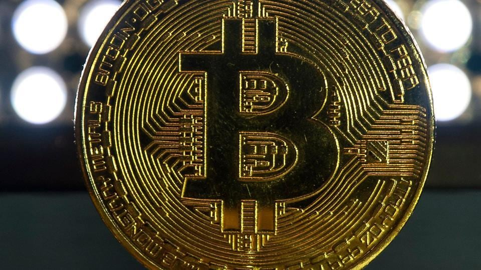 This file photo shows gold plated souvenir Bitcoin coins are arranged for a photograph in London.