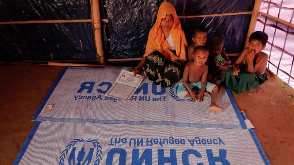 Roshid Jan, a Rohingya refugee who said she is not sure about her age, sits with her children at their shelter at the camp for widows and orphans inside the Balukhali camp near Cox's Bazar, Bangladesh, December 5, 2017.
