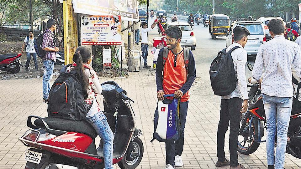 Students can be seen on two-wheelers without helmets at the entrance of the Wadia College campus.