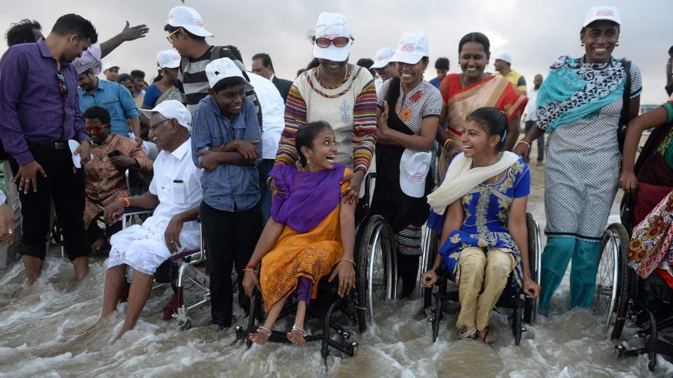 Physically challenged people react as they enjoy a day out at Elliot's beach on the occasion of International Day of Disabled Persons in Chennai on December 3, 2017.  (Arun Sankar / AFP)