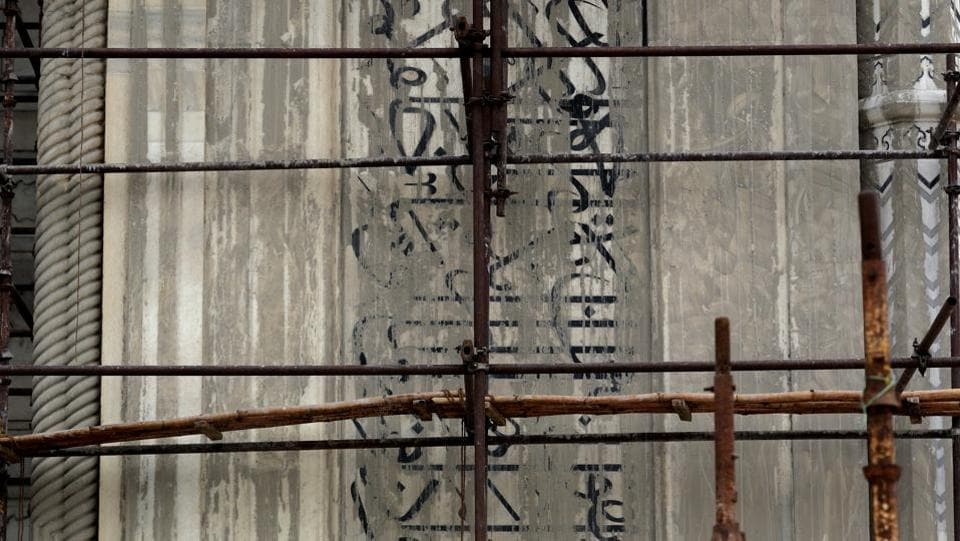 Verses from the Quran inscribed on the walls of the Taj Mahal are seen covered under fuller's earth in Agra. Bamboo scaffolding is not without precedent, considering it was used on the dome in the early 1940s when some conservation work was done. But rising pollution has blackened the dome's shaded areas which remain untouched by rains. (Manish Swarup / AP)