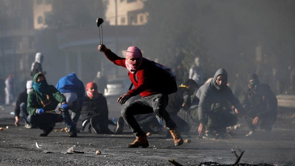 A Palestinian protester uses a sling to hurl stones towards Israeli troops during clashes near West Bank.