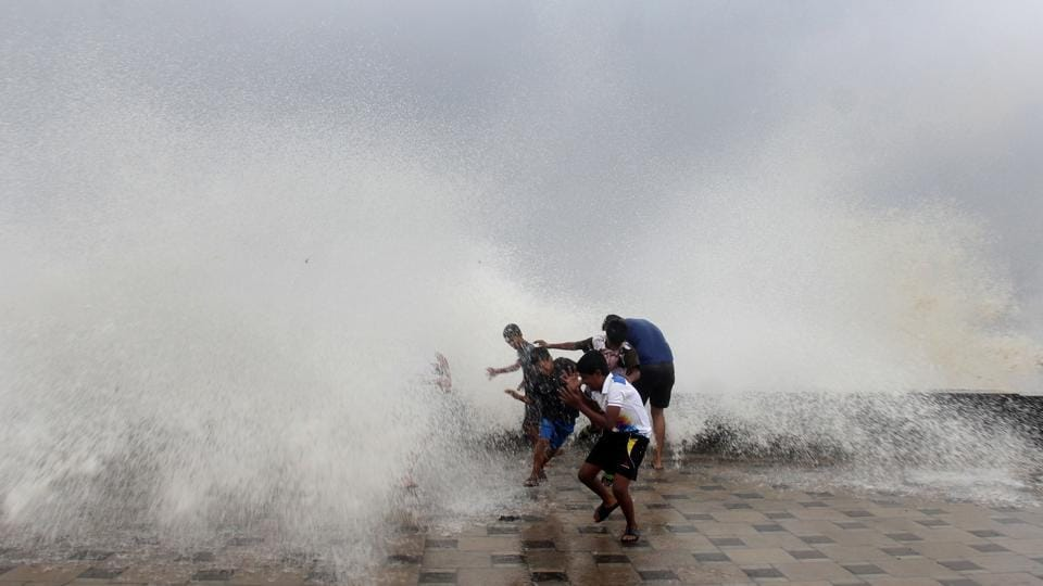 People enjoy high tide caused by Cyclone Ockhi  at Worli Seaface, in Mumbai on Tuesday. (Bhushan Koyande / HT Photo)