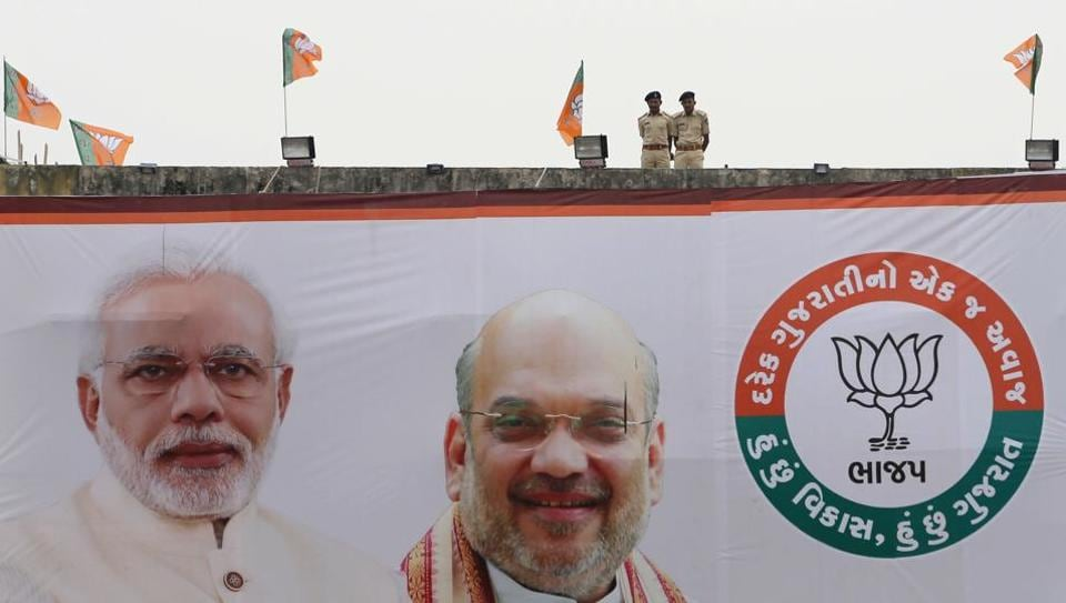 Policemen keep vigil from terrace of a building with a huge hoarding featuring Prime Minister Narendra Modi and Amit Shah during an election campaign rally at Surendranagar in Gujarat.
