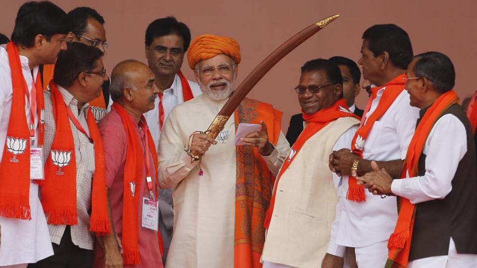 PM Narendra Modi (C) holds a sword presented to him during an election campaign rally at Dhandhuka in Gujarat on Wednesday.  (Ajit Solanki / AP)