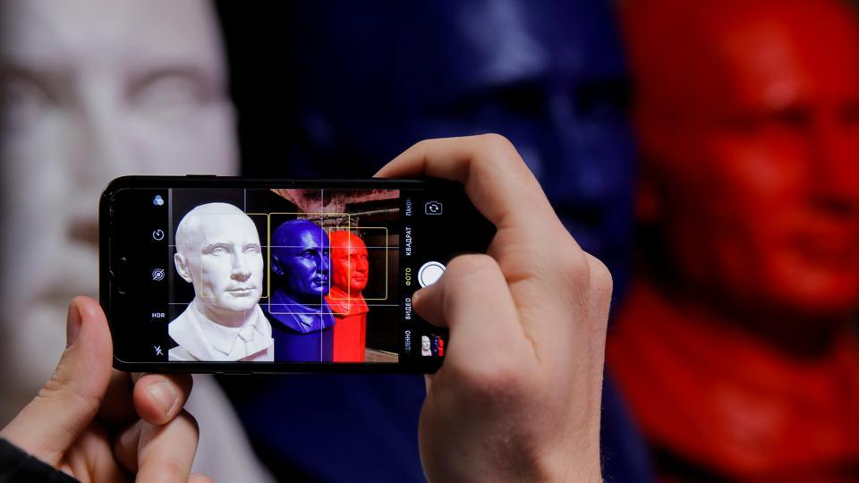 A man takes a picture of busts depicting Russian president Vladimir Putin in the colours of the Russian national flag at the