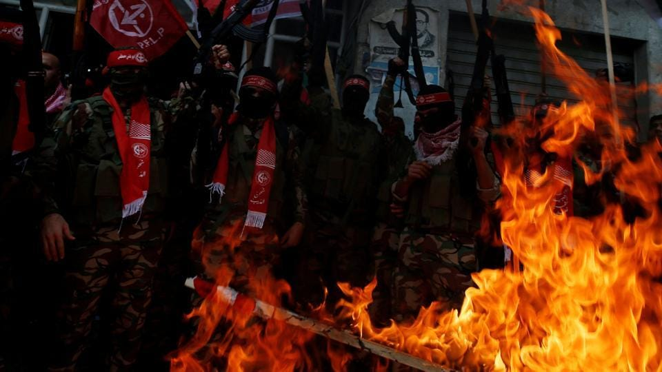 Palestinian militants of the Popular Front for the Liberation of Palestine burn representations of an Israeli flag and a US flag during a protest against US President Donald Trump's decision to recognise Jerusalem as the capital of Israel, in Gaza City December 7, 2017. REUTERS/Mohammed Salem