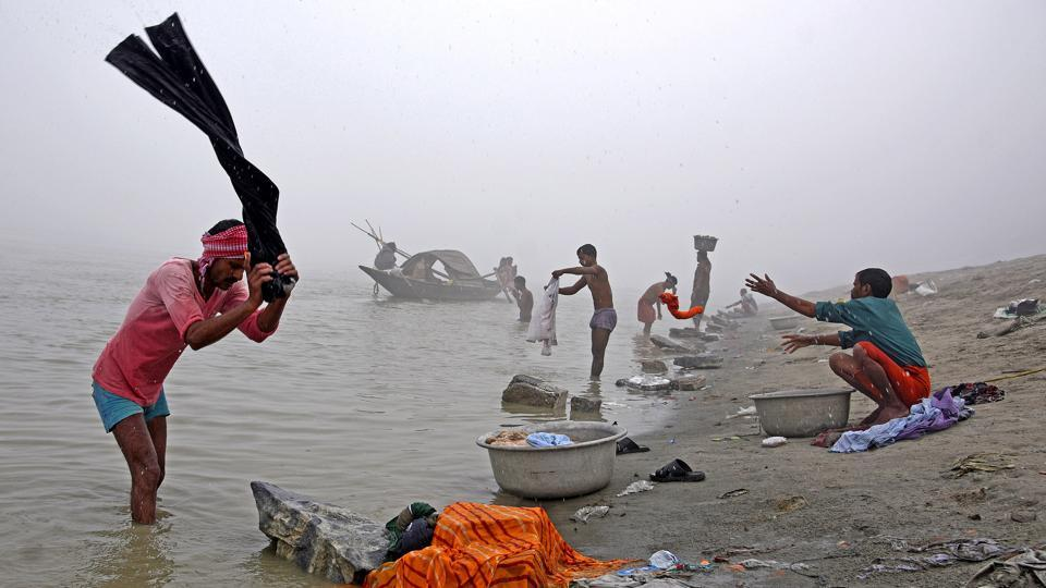 People wash clothes on the banks of the river Brahmaputra on a foggy winter morning in Guwahati on December 4, 2017. (Anuwar Hazarika / REUTERS)