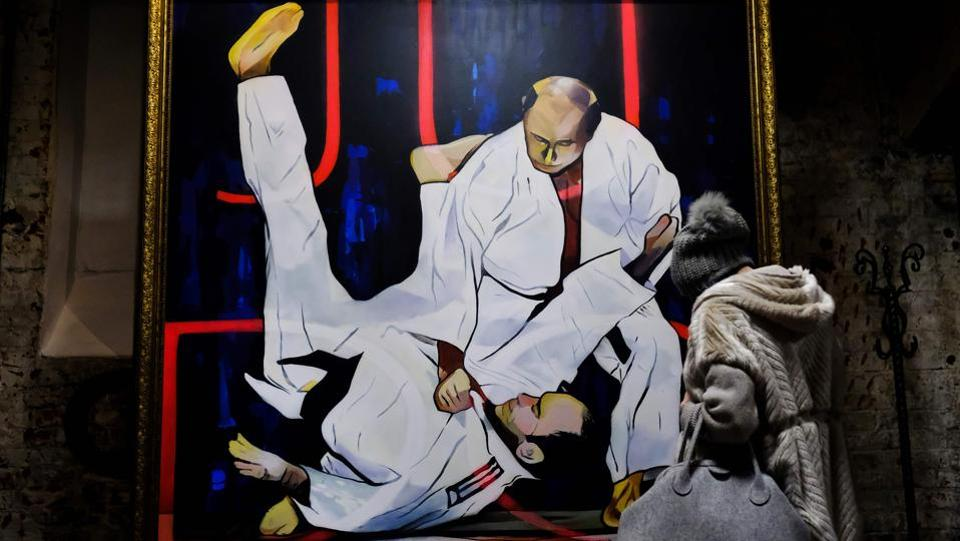 A visitor looks at a painting depicting Russian president Vladimir Putin, a reported black belt, take down an opponent in a Judo match. Putin's martial arts skills are the stuff of legend and receive extensive coverage within Russian media. (Yuri Kadobnov / AFP)