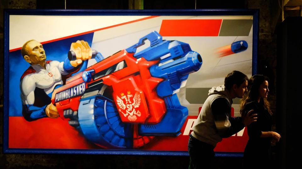 "Visitors stand next to a painting depicting a stoic Vladimir Putin brandishing a ""Putin Blaster"" at the exhibition. Hailed by allies as a leader who has restored national pride and expanded Moscow's international clout, no challenger appears capable of unseating the leader at the moment. (Yuri Kadobnov / AFP)"