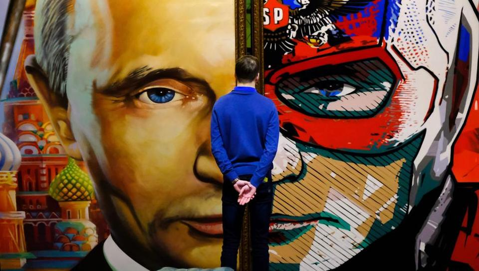 Part Russian president, part superhero --a man looks at a diptych of the Russian leader at the