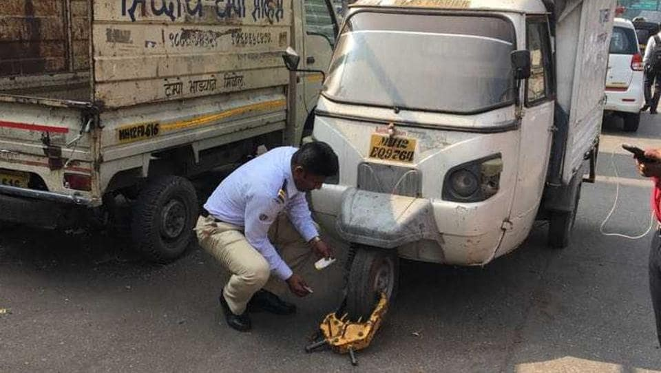 A traffic policeman puts on a tyre jammer on the front wheel of a goods vehicle in the city. The Pune traffic branch has launched a crackdown against violations at 28 spots, mostly chowks.