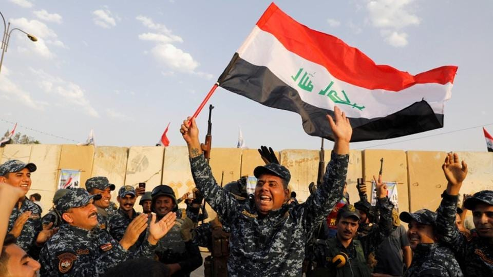A member of Iraqi Federal Police waves an Iraqi flag as they celebrate victory of military operations against the Islamic State militants in West Mosul, Iraq.