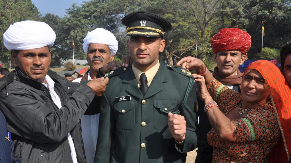 Parents of newly commissioned officer Ashok Kumar from Rajasthan formally removing covers of his batches during piping ceremony at Indian Military Academy in Dehradun.