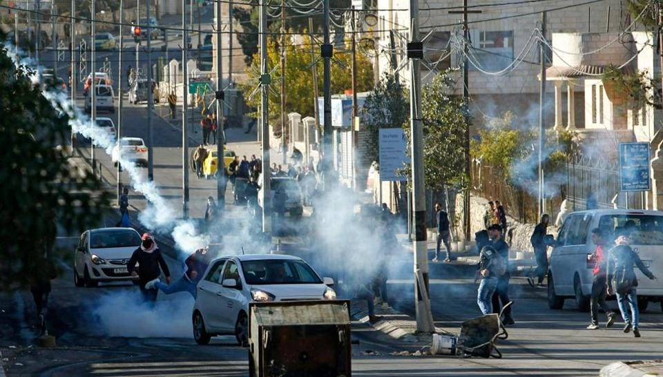 Palestinian protestors clash with Israeli forces near an Israeli checkpoint in the West Bank town of Bethlehem on December 9, 2017, following the US president's decision to recognize the city of Jerusalem as the capital of Israel.