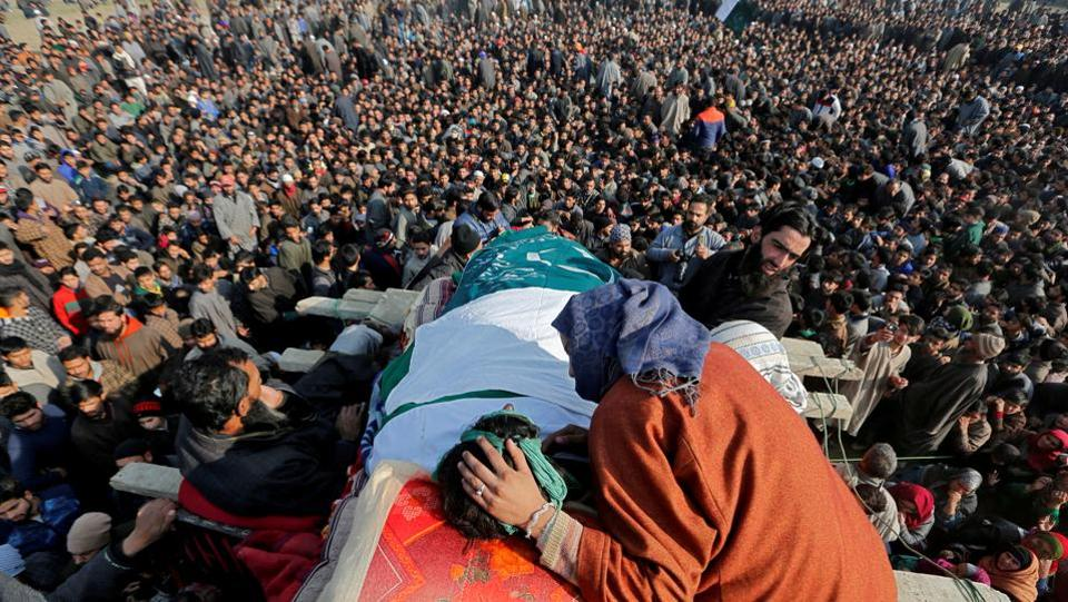 A woman sits next to the body of Yawar Bashir, a suspected militant --who according to the local media was killed in a gunbattle with Indian security forces on Monday-- during his funeral procession at Kulgam district on December 5, 2017. (Danish Ismail / REUTERS)