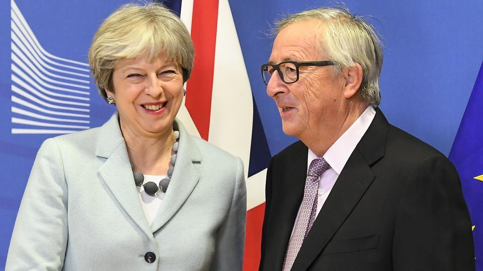 British Prime Minister Theresa May is welcomed by European Commission Jean-Claude Juncker at European Commission in Brussels on December 8, 2017.