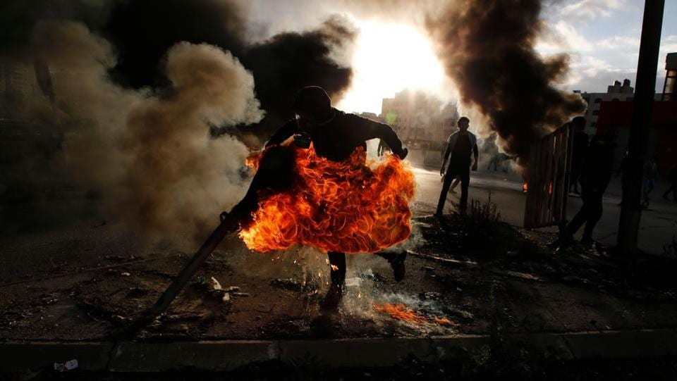 A Palestinian protester runs after catching fire during clashes with Israeli troops at a protest against US President Donald Trump's decision to recognize Jerusalem as the capital of Israel, near the Jewish settlement of Beit El, near the West Bank city of Ramallah on December 7, 2017. (Abbas Momani / AFP)