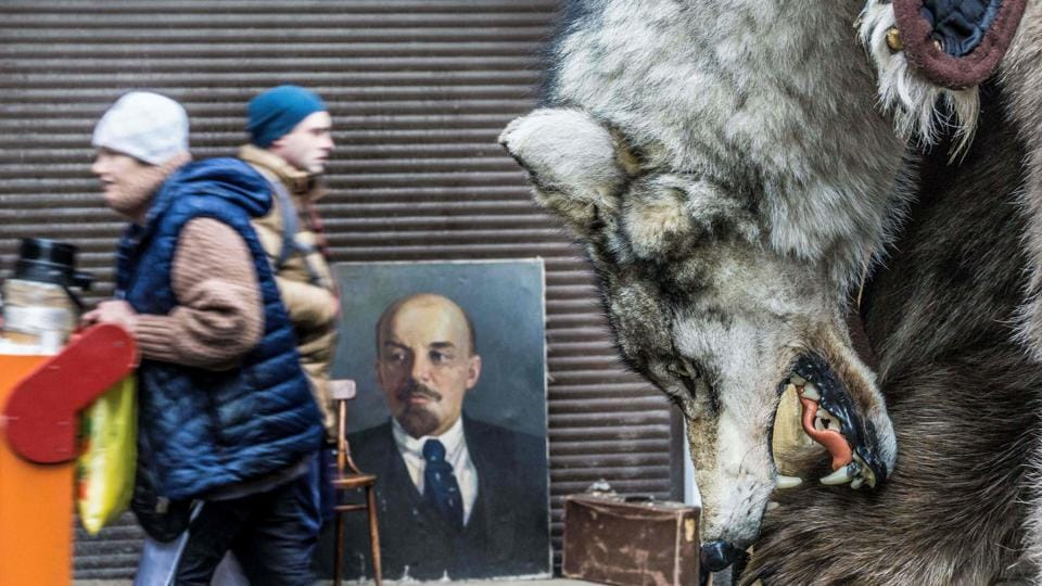 A wolf skin is on display for sale next to a painting of Russian communist revolutionary Vladimir Ilyich Ulyanov, also known as Lenin, at Izmailovo flea market in Moscow on December 3, 2017. (Mladen Antonov / AFP)