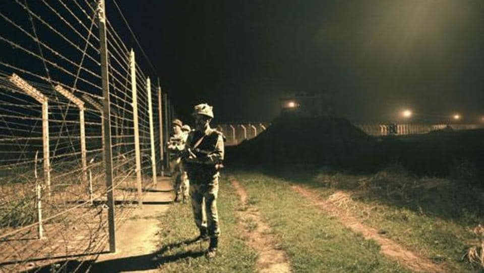 BSF soldiers standing guard during a night patrol near the fence at the India-Pakistan International Border at the outpost of Akhnoor sector, about 40 km from Jammu.