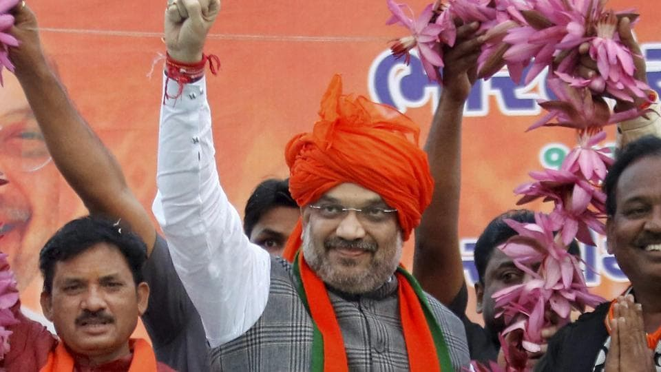 BJP members felicitate party's National President Amit Shah with 150 lotus garland during his election campaign rally for assembly election in Kheda on Saturday.