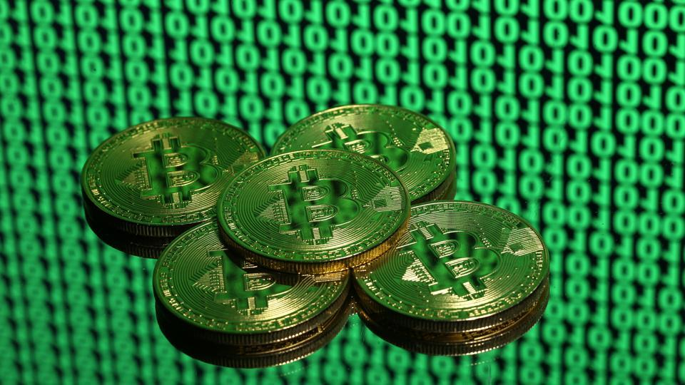 Tokens of the virtual currency Bitcoin are seen placed on a monitor that displays binary digits in this illustration picture, December 8, 2017.