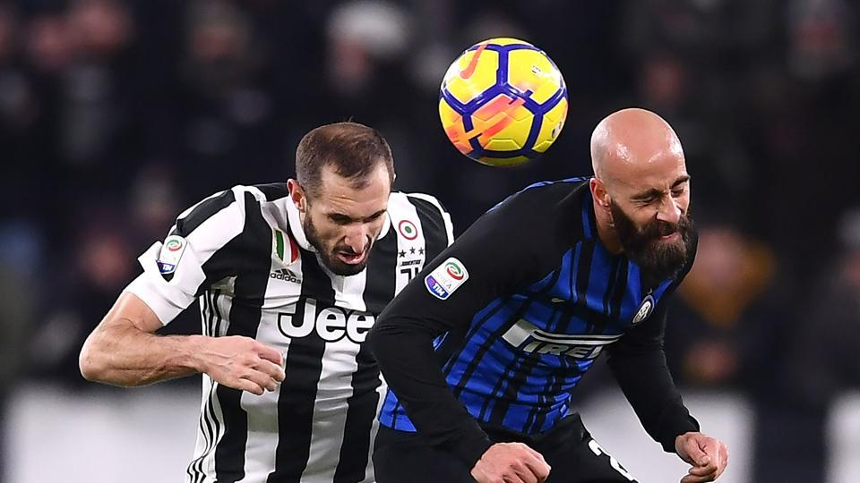 Juventus' defender Giorgio Chiellini (L) and Inter Milan's midfielder Borja Valero from Spain go for a header during the Italian Serie A football match on December 9, 2017 at the Allianz stadium in Turin.