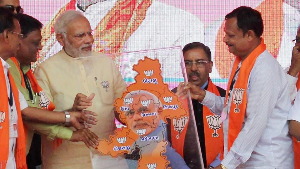 Prime Minister Narendra Modi being presented a memento during his election campaign rally for assembly election in Lunawada town of Mehsana, Gujarat on December 9.